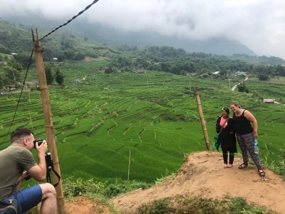 A Danish tourist, a black hmong guide, and rice terraces in the background